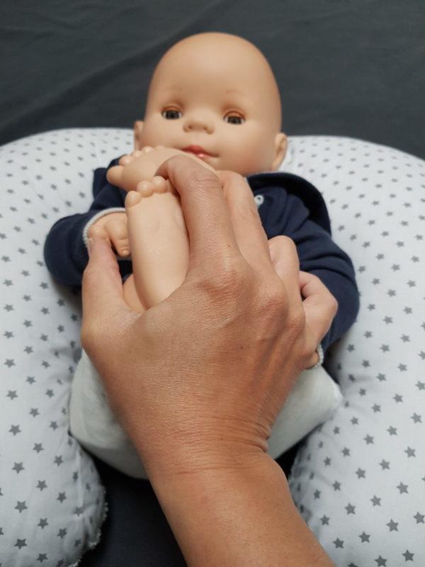 Apprendre le massage bébé sur un poupon